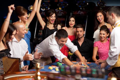 joueur masculin entouré d'un groupe de personne à une table de jeu
