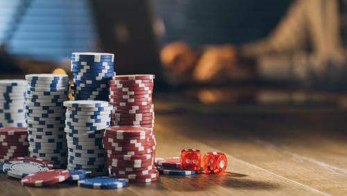 plusieurs piles de jetons de casino posés sur une table avec des dés rouges à côté