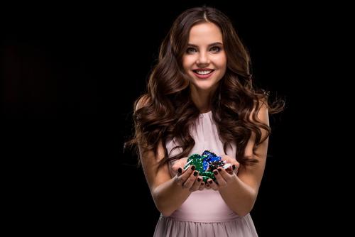 ravissante jeune femme tenant des jetons de casino dans sa main